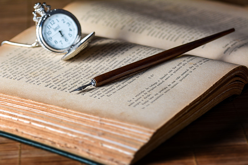 an old book with a pen an watch on it