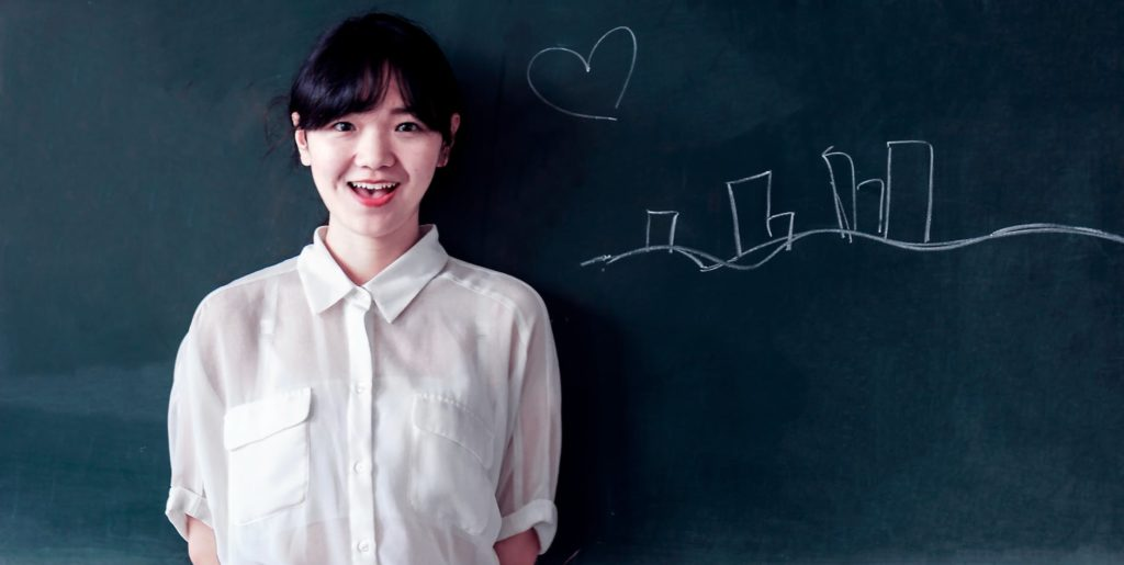 a girl standing next to the chalk board