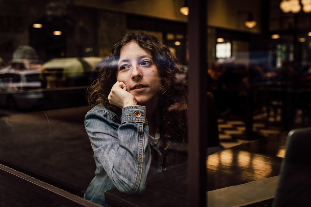 woman sitting in a cafe thinking