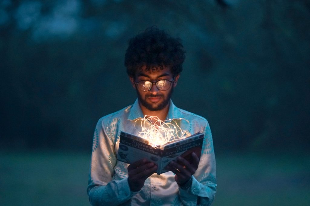 a man is holding a book with the string lights