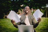 a guy with papers and a laptop in his hands