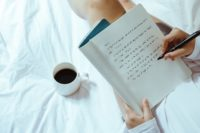 a girl is writing in a notebook sitting with a cup of coffee on a bed