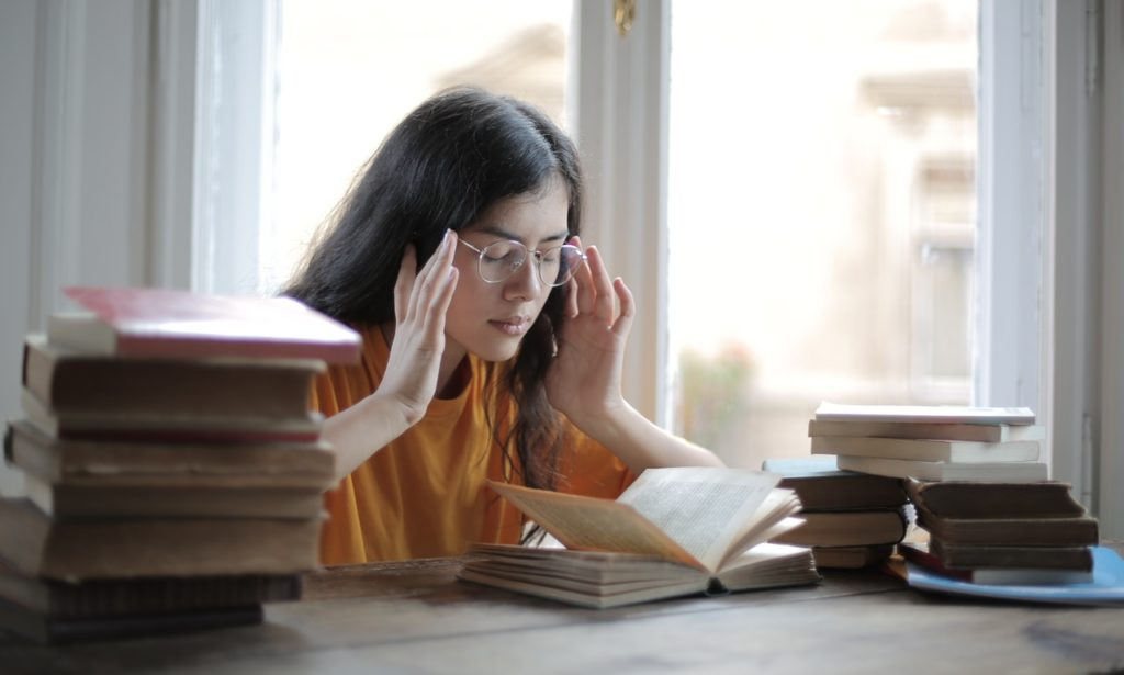 a girl is sitting with books opened